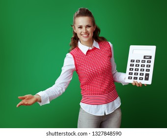 happy healthy student in grey jeans and pink sleeveless shirt with big white calculator inviting isolated on chalkboard green background. Finances and expenditures of modern education under control