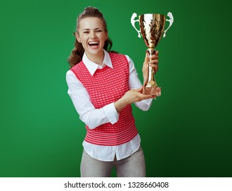happy healthy student in grey jeans and pink sleeveless shirt showing golden goblet on green background. challenging education