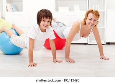 Happy and healthy woman exercising on large gymnastic balls with her son at home