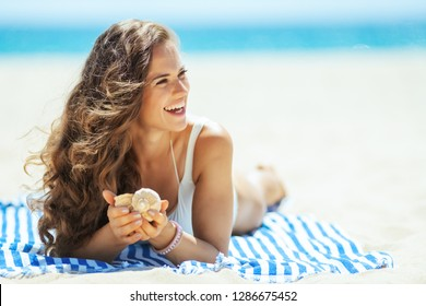 happy healthy woman in white swimsuit with seashell laying on a striped towel and looking aside on the seashore. successful shelling on vacation at the beach. quiet vacation heaven. Sun protected hair