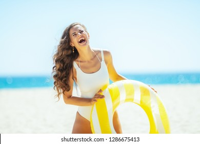 happy healthy woman in white swimwear on the ocean coast holding yellow inflatable lifebuoy. protect your hair from sun, heat, and humidity before heading to the beach. Sun protected hair.