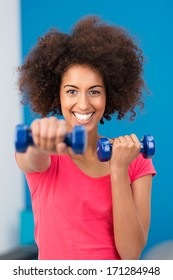 Happy healthy young African American woman working out in a gym with a pair of dumbbells extending her arm towards the camera with a beaming smile