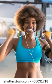 Happy healthy young African American woman working out in a gym with a pair of dumbbells