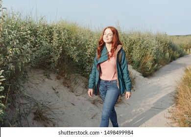 Happy healthy young woman on a coastal walk striding along a sandy footpath through scrub with closed eyes and a beaming smile in the autumn sunshine
