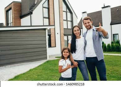 Happy heteroseksual family standing near their new house. Man holding keys from new apartment.
