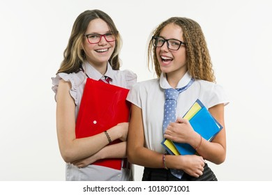 Happy high school friends closeup portrait. Pose on camera, in school uniform, with books and notebooks, on a white background.