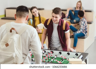happy high school students playing table football at school corridor