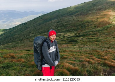 Happy hiker with a backpack on trekking in the hills.