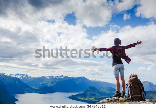 Happy hiker with her arms outstretched, freedom and happiness, achievement in mountains