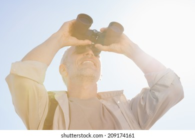 Happy hiker looking through binoculars on a sunny day