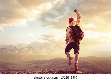 Happy hiker man jumps in winner pose against epic sunset mountains and sky