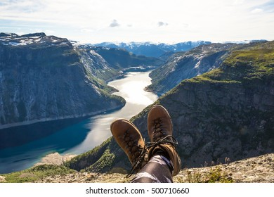 Happy hiker relax on Trolltunga. Mane enjoy beautiful lake and good weather in Norway.
