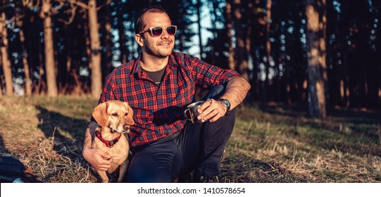 Happy hiker wearing plaid shirt and sunglasses resting on grass with small brown dog by the pine forest and drinking coffee during sunset
