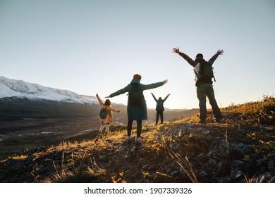 Glückliche Wanderer stehen mit hohen Armen und schauen auf Sonnenuntergangsberge