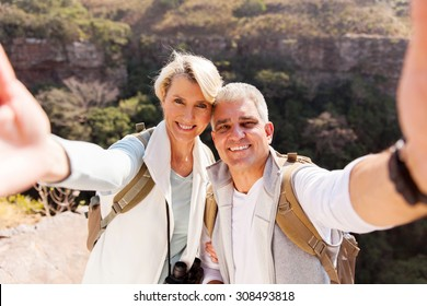 happy hiking couple taking selfie together on top of mountain
