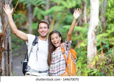 Happy hiking - hikers cheering joyful in forest. Cheerful excited hiker couple with arms raised up outstretched in joy smiling happy looking at camera. Multiethnic man and woman on Big Island, Hawaii.