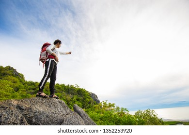 Happy hiking women stand on top of mountain with backpack enjoy sunrise