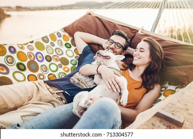 happy hipster couple with bulldog relaxing in hammock on the beach in sunset light, summer vacation. stylish family with dog cuddling and having fun, cute moments in summer evening