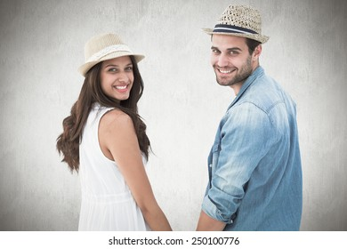 Happy hipster couple holding hands and smiling at camera against white background