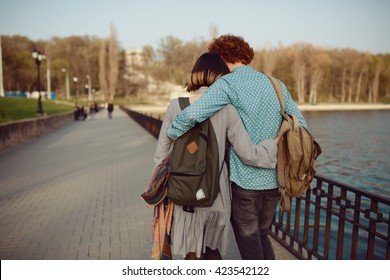 Happy hipster couple on holiday having fun and enjoy the time. Couple in love walking by the lake and talking, wearing modern clothes. Back view