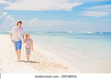 Happy hipster father and his small son having great quality family time enjoying white sand and the ocean on beautiful sunny day on summer holidays
