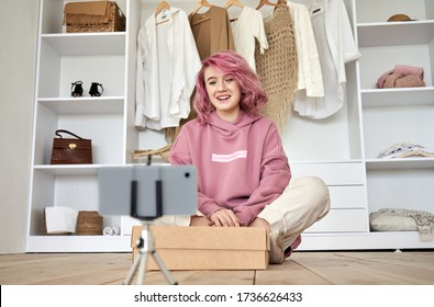 Happy hipster gen z teen girl fashion social media channel blogger with pink hair wear hoodie recording unboxing vlog on phone video camera tutorial sit on floor with online store clothes order box.