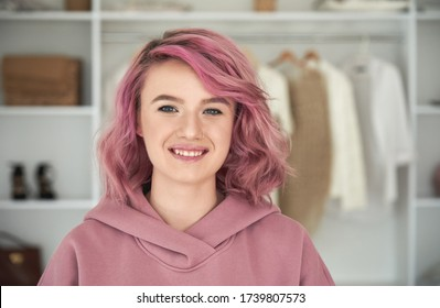 Happy hipster gen z teen girl fashion designer, stylist with pink hair and piercing wearing hoodie looking at camera in front of modern clothes wardrobe closet, face head shot close up portrait.