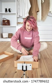 Happy hipster gen z teen girl fashion social media channel blogger pink hair wear hoodie record unboxing vlog on phone video camera tutorial sit on floor open online store clothes order box, vertical.