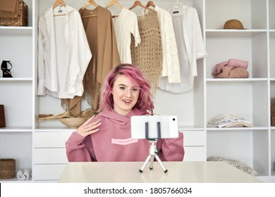 Happy hipster gen z woman fashion social media channel blogger with pink hair wear hoodie speaking recording video blog on phone video camera vlog tutorial sitting near clothes wardrobe closet.