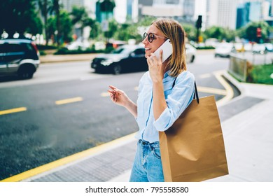 Happy hipster girl in eyewear walking on street talking on phone, cheerful young woman strolling in downtown carrying shopping bag with copy space for brand name or label having mobile conversation