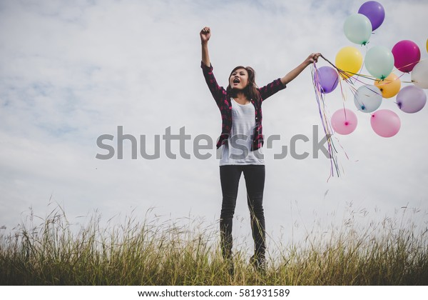 Happy hipster girl jumping with colorful toy balloons outdoors. Young woman having fun in green field against blue sky. Women freedom lifestyle concept.