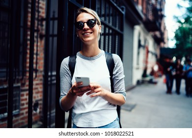 Happy hipster girl sending message via smartphone enjoying leisure strolling, smiling female tourist in sunglasses satisfied with internet connection in roaming chatting online while sightseeing