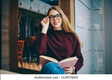 Happy hipster girl sitting at university cafeteria with book in hands and looking away with cute smile on face while holding fashionable eyeglasses, successful woman student studying indoors