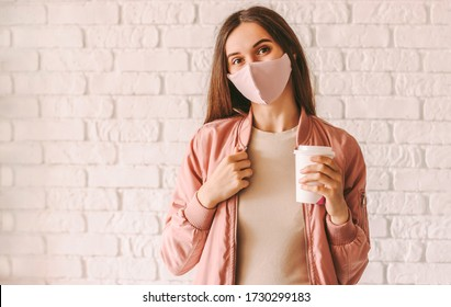 Happy hipster girl in stylish medical face mask and jacket drink coffee from paper cup. Beautiful trendy woman in pink protective face mask hold disposable cup of coffee or tea. Quarantine lifestyle