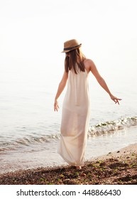 Happy hipster girl walking on a sea beach, long white casual dress and hat