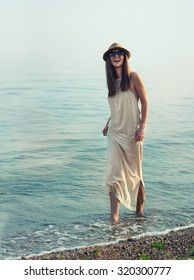 Happy hipster girl walking in sea water