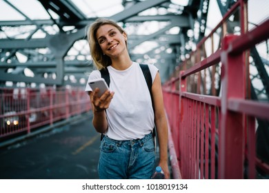 Happy hipster girl in white t-shirt with copy space for brand name or label standing with smartphone on bridge, smiling young woman sending text messages via mobile phone walking on urban setting