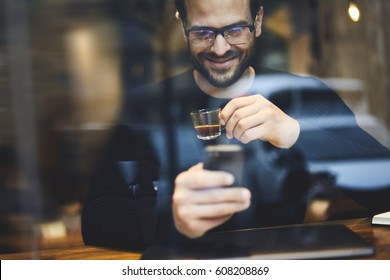 Happy hipster guy with smile looking on smartphone screen watching funny video and enjoying strong espresso in urban cozy coffee shop. Smiling young man having video conversation with family members