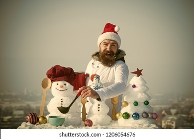 Happy hipster with ladle in white uniform. Cook, snowmen and snow xmas tree on blue sky. Cooking and diet concept. Christmas and new year holidays food. Man in santa hat ladling soup on winter day.