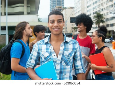 Happy hipster male student with group of multi ethnic young adults in city