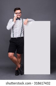 Happy hipster man communicating over mobile phone. Handsome man posing with blank poster in full length over grey background.