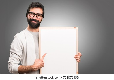 Happy Hipster man holding an empty placard on grey background