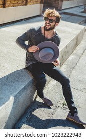 Happy hipster man holding hat while sitting on the stairs