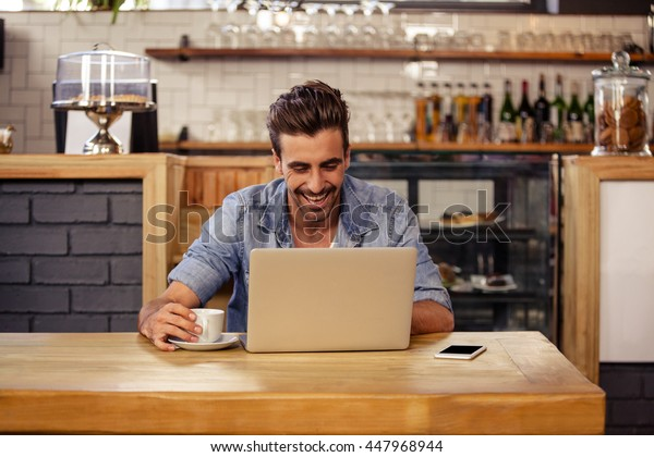 Happy hipster man using tablet and drinking coffee at cafe