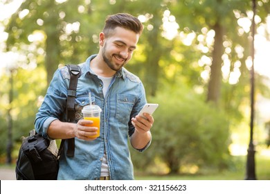 Happy hipster man walking in autumn park and smiling. Short-haited man looking at mobile phone's screen and enjoying reading messages.
