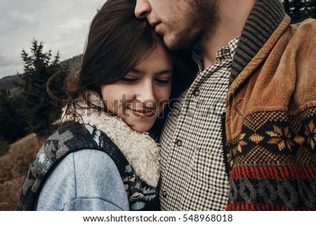 happy hipster traveler couple hugging on top of mountains. romantic moment of stylish family. wanderlust and travel concept with space for text.