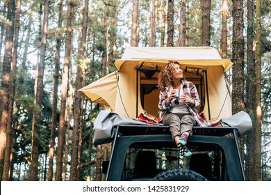 Happy hipster traveler people enjoying the alternative vacation - car with tent on the roof and beautiful young woman sit down outside looking at the forest around - outdoor activity
