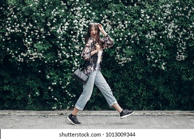 happy hipster woman with sunglasses having fun at blooming bush with white flowers of spirea. boho girl jumping and smiling in modern clothes, emotional moment. space for text