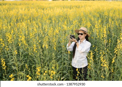 happy hipster woman with sunglasses having fun at blooming bush with white flowers