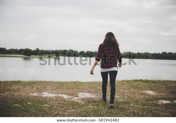 happy hipster woman walking through to the lake on background of summer field.